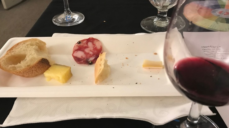 Partly eaten bread and cheese on a plate with a glass of red wine