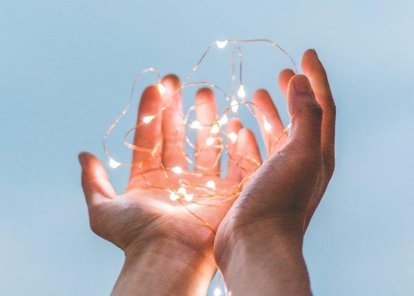 Open hands holding lights